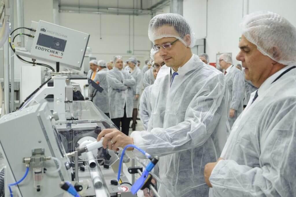 """A """"kotonba"""" öltözött, mindenhez is értő külgazdasági és külügyminiszter a Tu-Plast Tubusgyártó Kft. új üzemcsarnokának avatásán Debrecenben (MTI Fotó: Czeglédi Zsolt)"""