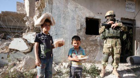 Szíriai gyerekek humanitárius szervezet által adományozott és az országban állomásozó orosz haderő által kiosztott élelmiszersegéllyel egy orosz katona társaságában a szíriai Hama tartománybeli Kaukab faluban 2016. május 4-én. (MTI/EPA/Szergej Csirikov)