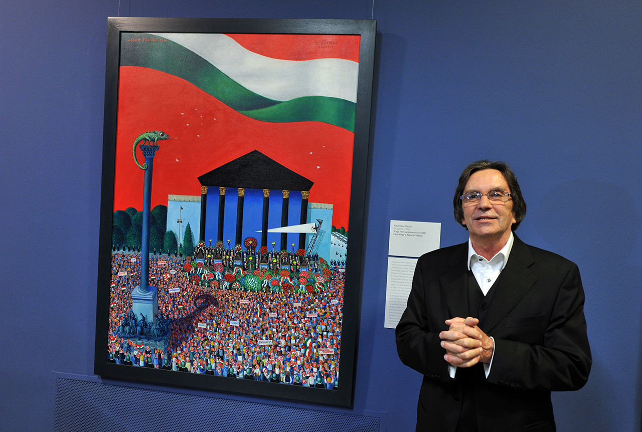 """Hungarian theater director and government commissioner Imre Kerenyi presents a picture 'Imre Nagy Reburial' from a collection of 15 paintings in the Hungarian National Gallery during opening for public on January 3, 2012. This canvas depicts Hungarian Prime Minister Viktor Orban. These pictures show Hungary's recent events including police action against protesters in 2006 and the red mud diseaster in 2010. Art critics slammed the pictures, ordered for 1.6 million forints (5,000 euros, $6,600) each, for being """"horribly ecclectic, messy in their styles and approach"""". As the government celebrated the new constitution at a gala event in Budapest's Opera, tens of thousands demonstrated against the act, which critics say curb democracy and cement Orban's power. AFP PHOTO / ATTILA KISBENEDEK"""