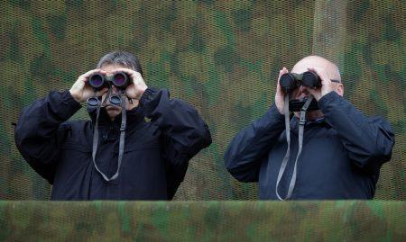 Hadgyakorlat-mustra: Hende Csaba egykori honvédelmi miniszter védőkupakon keresztül is látja azt, amit Orbán csak kupak nélkül (Fotó: AFP/Kisbenedek Attila)
