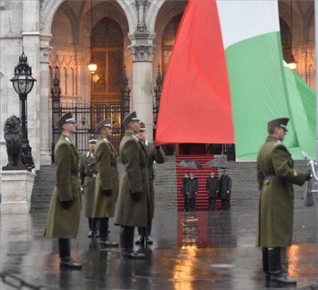 Katonai tiszteletadás mellett felvonják Magyarország nemzeti lobogóját az 1956-os forradalom és szabadságharc kitörésének 61. évfordulóján a Parlament előtti Kossuth Lajos téren 2017. október 23-án. A háttérben Áder János és Kövér László (MTI Fotó: Illyés Tibor)