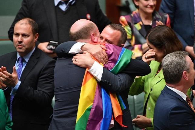 Képviselők ünnepelnek a canberrai parlamentben 2017. december 7-én, miután az ausztrál képviselőház megszavazta az azonos neműek házasságát engedélyező törvényt nyolc nappal azután, hogy a szenátus is elfogadta azt. Az ausztrálok ősszel levélszavazás útján nyilváníthattak véleményt a melegházasságról, a szavazók 61,6 százaléka a támogatását fejezte ki. (MTI/EPA/Mick Tsikas)